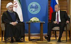 Sur cette photo du 9 juin 2018, le président russe Vladimir Poutine, (à droite), discute avec le président iranien Hassan Rouhani pendant une réunion à Qingdao, en Chine. (AP Photo/Alexander Zemlianichenko, Pool, File)