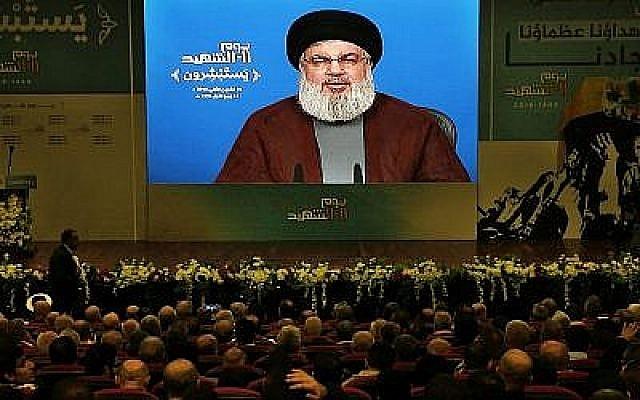 Des militants de l'organisation terroriste du Hezbollah, soutenue par l'Iran, écoutent le discours du dirigeant du Hezbollah Hassan Nasrallah, via une liaison vidéo, lors d'un rassemblement marquant la Journée des martyrs du Hezbollah, dans une banlieue sud de Beyrouth au Liban, le 10 novembre 2018. (AP Photo/Bilal Hussein)