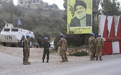 Des soldats de la paix indonésiens de l'ONU devant une affiche du leader du Hezbollah, Sheikh Hassan Nasrallah, lors d'une patrouille du côté libanais de la frontière israélo-libanaise dans le village de  Kfar Kila, au sud du Liban, le 4 décembre 2018 (Crédit : AP/Mohammed Zaatari)