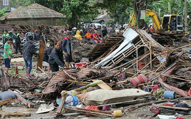Des résidents inspectent une maison endommagée par un tsunami, à Carita, en Indonésie, le 23 décembre 2018 (AP Photo)