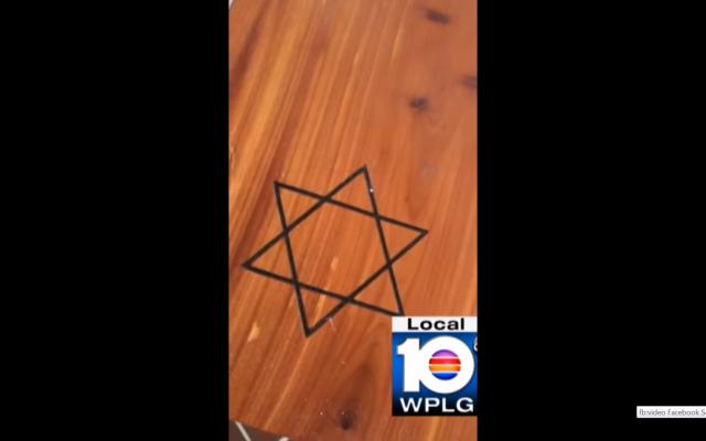 Extrait d'une vidéo ayant entraîné la suspension d'un agent de police de Miami ,qui a jeté à la poubelle un Tanakh et une boîte avec l'Etoile de David (Capture d'écran : Facebook)