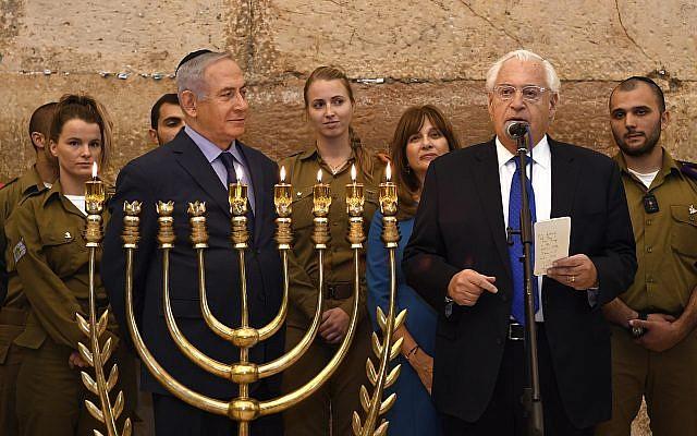 Le Premier ministre Benjamin Netanyahu a rejoint l'ambassadeur américain en Israël David M. Friedman et son épouse Tammy au mur Occidental pour une cérémonie d'allumage de bougie pour Hanoukka qui a célébré également le premier anniversaire de la reconnaissance de Donald Trump de Jérusalem, le 6 décembre 2018 (Crédit : Koby Gideon/GPO)