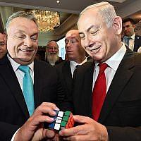 Le Premier ministre Benjamin Netanyahu et le Premier ministre hongrois Viktor Orban, (à gauche), avec un rubik's cube lors d'un forum commercial israélo-hongrois à Budapest, en Hongrie, le 19 juillet 2017 (Crédit : Haim Zach/GPO/Flash90)