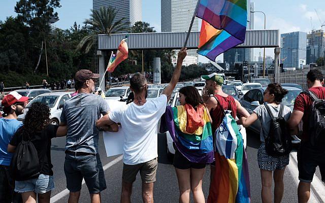 Les membres de la communauté LGBT et leurs soutiens lors d'une manifestation pour protester contre une nouvelle loi sur la GPA excluant les homosexuels à la Knesset, à Tel Aviv, le 22 juillet 2018 (Crédit : Tomer Neuberg/Flash90