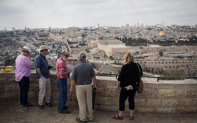 Des touristes écoutent un guide sur le belvédère du Mont des Oliviers surplombant la Vieille Ville de Jérusalem, le 11 octobre 2018. (Hadas Parush/Flash90)