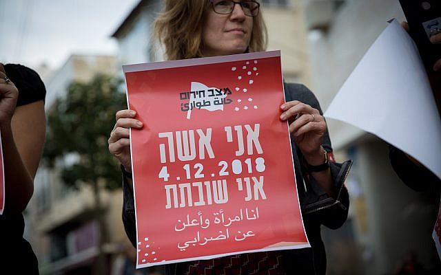 Une femme tient une pancarte disant qu'elle est en grève lors d'une manifestation à Tel Aviv, le 2 décembre 2018 (Crédit : Miriam Alster/Flash90)