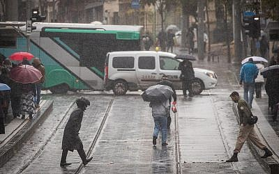 Des gens marchent Route de Jaffa, à Jérusalem, sous la pluie, le 6 décembre 2018 (Crédit : Yonatan Sindel/Flash90)