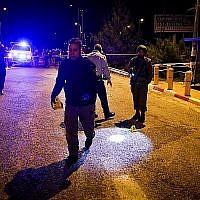 Des soldats israéliens et la police inspectent la scène d'un attentat terroriste à l'entrée de l'implantation israélienne d'Ofra, en Cisjordanie, le 9 décembre 2018 (Crédit : Ofer Meir/Flash90)