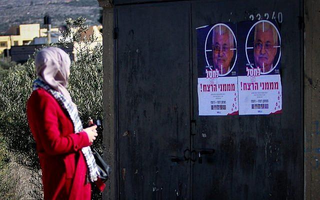 """Une Palestinienne marche près de posters montrant le président palestinien  Mahmoud Abbas  avec un texte disant """"Eliminez ceux qui sponsorisent le terrorisme"""" au carrefour de Hawara, au sud de la ville de Naplouse, en Cisjordanie, le 11 décembre 2018 (Crédit : Nasser Ishtayeh/Flash90)"""