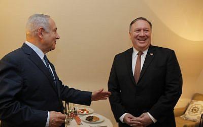 Le Premier ministre Benjamin Netanyahu et le secrétaire d'Etat américain  Mike Pompeo devant une ménorah au second soir de la fête de Hanoukka, au cours de leur rencontre en marge d'une conférence de l'OTAN à Bruxelles, en Belgique, le 13 décembre 2018 (Crédit :  Gaby Farkash/GPO)
