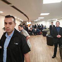 Le ministre de la Communication, Ayoub Kara, reçoit des soins médicaux à l'extérieur du plénum de la Knesset après s'être effondré, le 12 décembre 2018. Le Premier ministre Benjamin Netanyahu, qui était alors en séance plénière, est visible assis à droite sur la photo. (Autorisation)
