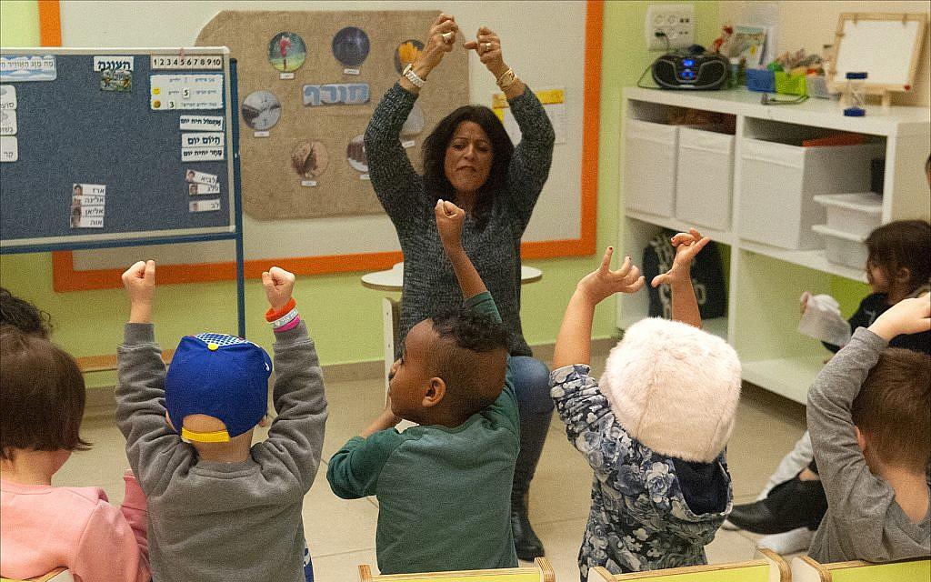 """Dorit Zach, enseignante au jardin d'enfants """"Daycare of Dreams"""" de Larger Than Life à Ramat Gan, fait chanter en chœur des enfants atteints de cancer une chanson en hébreu. (Larry Luxner/ Times of Israel)"""