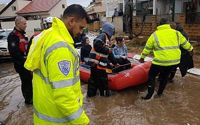 Des sauveteurs évacuent les habitants de Ahiezer de leurs maisons inondées, le 7 décembre 2018. (Crédit : police israélienne)