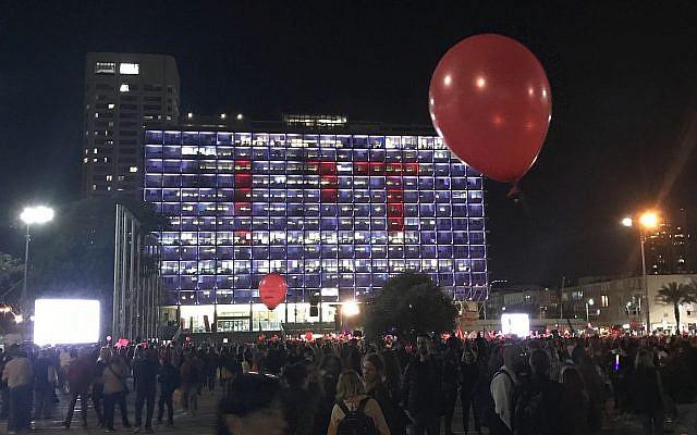 """La mairie de Tel Aviv éclairée par la projection du mot """"Assez"""" en hébreu alors que des milliers de  manifestantes sont réunies sur la place Rabin de Tel Aviv dans le cadre d'une grève nationale de protestation contre les violences faites aux femmes, le 4 décembre 2018 (Crédit : Luke Tress/Times o fIsrael)"""