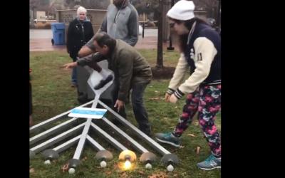 Des personnes aident à remettre sur pied une hannoukiah qu a été renversée à Cambrigde, dans le Massachusetts, le 3 décembre, 2018 (Crédit : capture d'écran/Twitter)