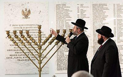 Le Rabbi David Lau, grand rabbin ashkénaze d'Israël, allume des bougies de Hanoukka au Sejm, chambre basse du parlement polonais, le 5 décembre 2018 (Crédit : Eli Mandelbaum via JTA)
