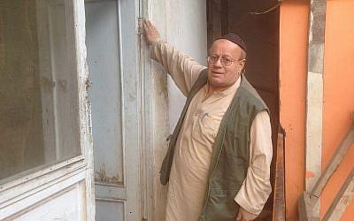 Zabolon Simantov touche la mézuzah accrochée à sa porte, un signe affirmé de vie juive  (Crédit : Ezzatullah Mehrdad/ Times of Israel)