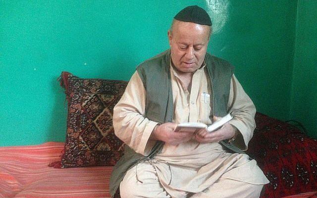 Zabolon Simantov récite la prière Shema écrite dans son livre de prières, à son domicile dans la dernière synagogue de Kaboul (Crédit :  Ezzatullah Mehrdad/ Times of Israel)