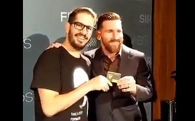 Lionel Messi (à droite), star du football argentin, reçoit sa carte de membre du fan club du Beitar Jerusalem des mains du propriétaire du club, Moshe Hogeg, lors d'un événement à Barcelone, Espagne, en décembre 2018. (Capture d'écran : Twitter)