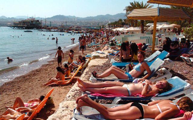 Des touristes et des Israéliens sur la plage d'Eilat. (Crédit : Nati Shohat/Flash90)