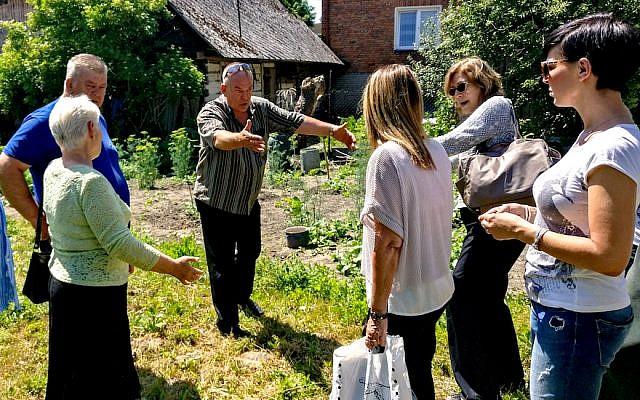 Totko Teklak montre à un visiteur Israël où son père a caché la mère du visiteur pendant la Shoah, en Pologne, en juin 2017. (Crédit :Lea Hirsch)