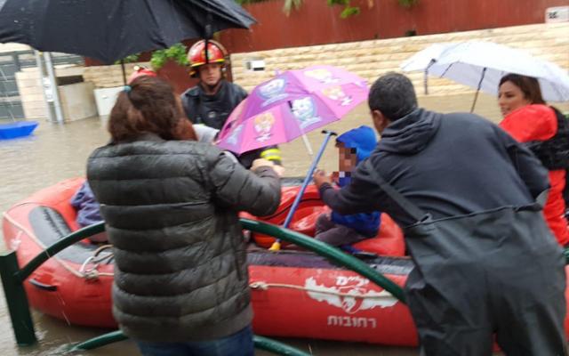 Des enfants asauvés d'une inondation par  bateau,  à cause d'importantes précipitions le 6 décembres 2018. (Crédit ; capture d'écran Hadashot)