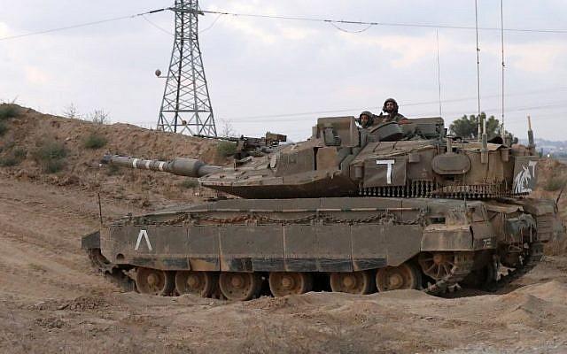 Des soldats israéliens se trouvent dans la tourelle d'un char de combat Merkava près du kibboutz de Nahal Oz, le long de la frontière avec la bande de Gaza, le 20 juillet 2018. (AFP PHOTO / JACK GUEZ)