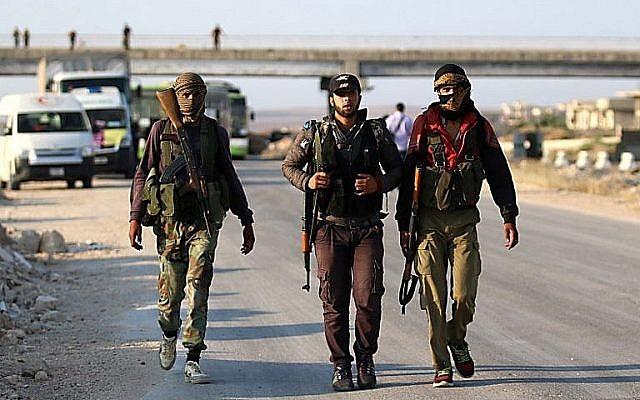 Des combattants rebelles syriens de la province de Quneitra au carrefour Morek, où ils attendent d'être transférés dans les provinces d'Idlib et d'Alep, le 21 juillet 2018 (Crédit : AFP Photo/Aaref Watad)