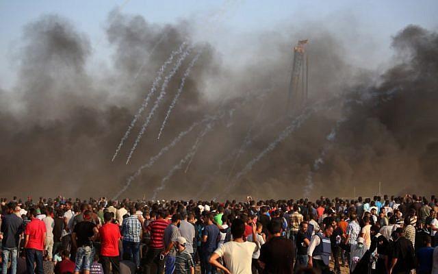 Des Palestiniens réagissent alors que des grenades lacrymogènes tirées par les forces israéliennes pleuvent pendant les affrontements le long de la clôture de la frontière israélienne, à l'est de la ville de Gaza, le 28 septembre 2018. (AFP Photo/Said Khatib)