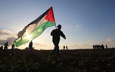 Un manifestant palestinien porte un drapeau national lors d'une manifestation près de la frontière entre Israël et Khan Younès dans le sud de la bande de Gaza, le 21 décembre 2018. (Photo par SAID KHATIB / AFP)