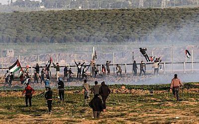 Des manifestants palestiniens tentent de franchir la barrière de sécurité avec Israël lors d'affrontements à la suite d'une manifestation le long de la frontière à l'est de la bande de Gaza le 4 janvier 2019. (Crédit : Saïd Khatib/AFP)