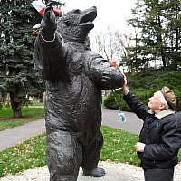"""Wojciech Narebski ancien soldat polonais de 93 ans, devant un monument représentant un ours brun qui """"servait"""" dans avec lui dans l'armée polonaise durant la Seconde guerre mondiale, le 14 novembre 2018. (Crédit : Janek SKARZYNSKI / AFP)"""