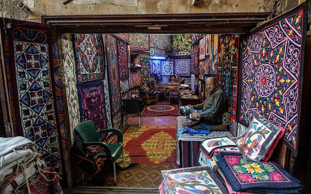 Un artisan égyptien travaille sur ses tapisseries, dans la rue Al-Khayamiya, au Caire, le 18 décembre 2019. (Crédit : Mohamed el-Shahed / AFP)