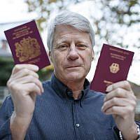 L'animateur TV Nick Ross avec son passeport allemand et son passeport britannique, le 5 novembre 2018. (Crédit : TOLGA AKMEN / AFP)