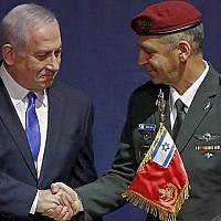 Le nouveau chef d'Etat-major Aviv Kochavi, à droite, serre la main au Premier ministre Benjamin Netanyahu lors d'une cérémonie de passation de pouvoir au siège du ministère de la Défense à Tel Aviv (Crédit : JACK GUEZ / AFP)