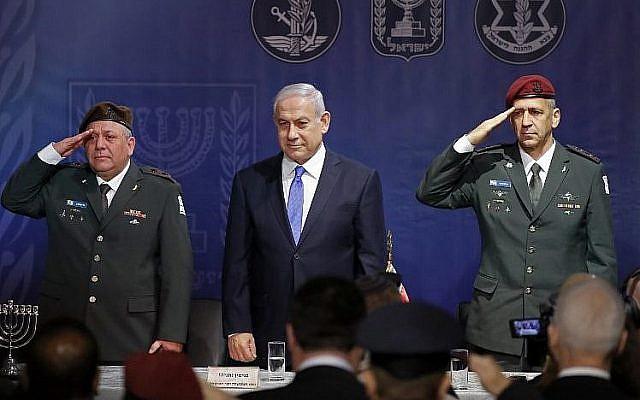 Le chef d'Etat-major sortant Gadi Eizenkot, à gauche, le Premier ministre Benjamin Netanyahu et le nouveau chef d'Etat-major Aviv Kochavi, à droite, lors de la cérémonie d'investiture de ce dernier au siège du ministère de la Défense de Tel Aviv, le 15 janvier 2019 (Crédit :  JACK GUEZ/AFP)