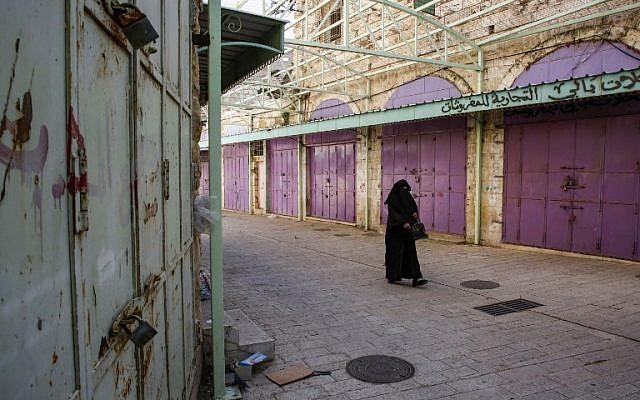 Une Palestinienne marche devant les boutiques fermées pour cause de grève contre le système de sécurité sociale proposé par l'AP, à Hébron, le 15 janvier 2019. (Crédit : HAZEM BADER / AFP)