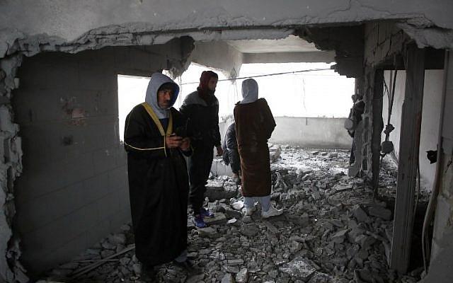 Des Palestiniens inspectent la maison d'un homme accusé d'avoir poignardé à mort en septembre un Israélien d'origine américaine, après sa démolition partielle par les forces israéliennes le 18 janvier 2019, dans le village de Yatta en Cisjordanie (HAZEM BADER / AFP)