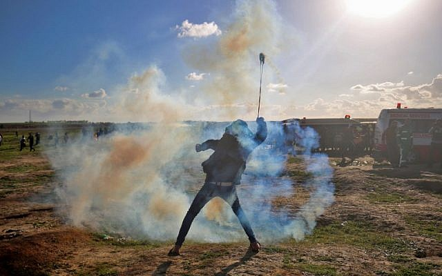Un émeutier palestinien se sert d'une fronde devant les gaz lacrymogènes lancés par l'armée israélienne lors d'une émeute le long de la frontière en Gaza et Israël, le 18 janvier 2019. (Crédit : SAID KHATIB / AFP)