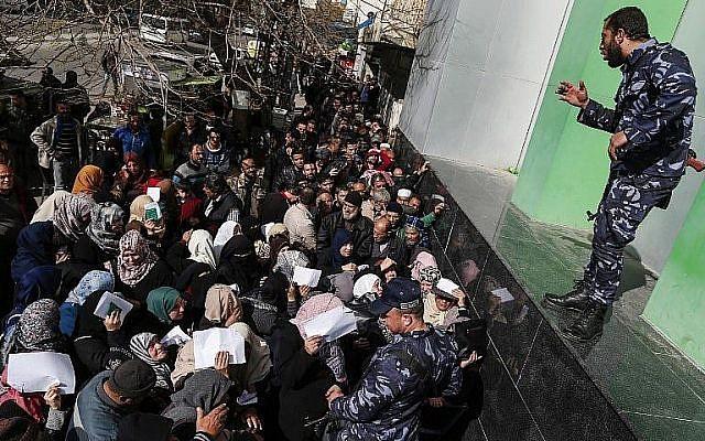 Les forces de sécurité fidèles au Hamas organisent une file d'attente devant le bureau de poste central de la ville de Gaza le 26 janvier 2019, alors que les Palestiniens se rassemblent pour recevoir une aide financière du Qatar. (Crédit : Mahmud Hams/AFP)