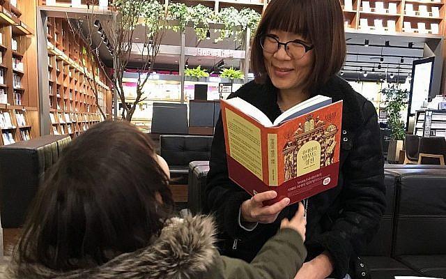Une Sud-Coréenne et son enfant lisent des livres sur le Talmud dans une librairie de Séoul. (Tim Alper via JTA)