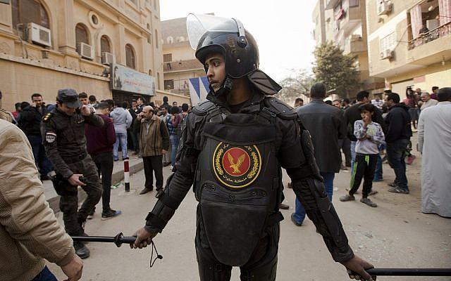 Un, policier monte la garde devant l'église  Mar Mina après une attaque meurtrière revendiquée par le groupe de l'Etat islamique à Helwan, au Caire, en Egypte, le 29 décembre 2017 (Crédit :  AP Photo/Amr Nabil)