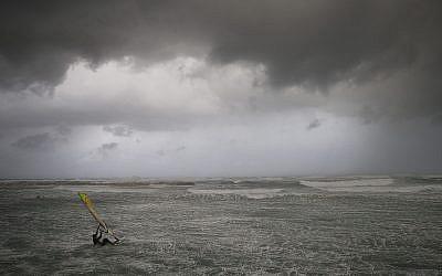 Un véliplanchiste surfe sur les vagues de la mer Méditerranée à Tel Aviv le 16 janvier 2019. (AP Photo/Oded Balilty)
