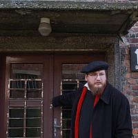 Piotr Cywinski, directeur du musée de l'ancien camp de la mort nazi d'Auschwitz-Birkenau, ferme la porte du baraquement numéro 10 préservé tel quel depuis les atrocités nazies, à  Oswiecim, en Pologne, le 11 janvier 2017 (Crédit : AP Photo/Czarek Sokolowski)  )