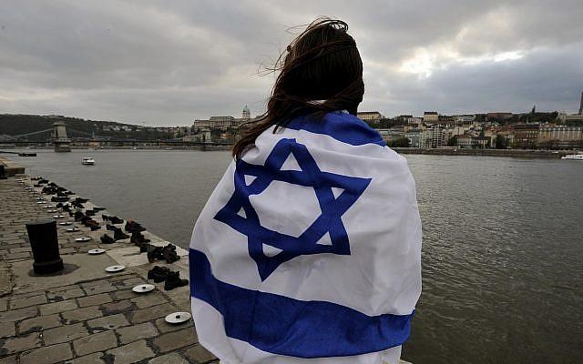 Une jeune fille juive hongroise, couverte d'un drapeau israélien, devant le mémorial de chaussures commémorant les victimes de la Shoah sur la rive du Danube lors de la commémoration de la Journée de la Shoah en Hongrie, mercredi 16 avril 2008 à Budapest (Crédit : AP/Bela Szandelszky)