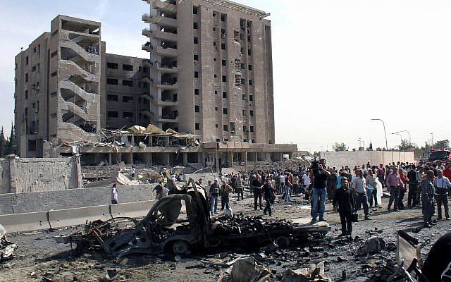 Illustration : des Syriens rassemblés devant une immeuble du renseignement militaire où deux bombes ont explosé, à Damas, le 10 mai 2012. (Crédit : Bassem Tellawi/AP)
