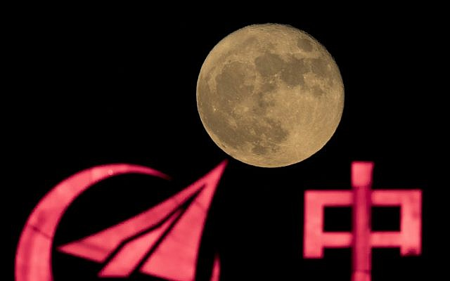 La super-lune s'élève sur le logo d'AVIC - ou Aviation Industry Corp, - compagnie d'état chargée des missions spatiales avec équipage en Chine, à Pékin, le 15 novembre 2016 (Crédit : AP Photo/Ng Han Guan)