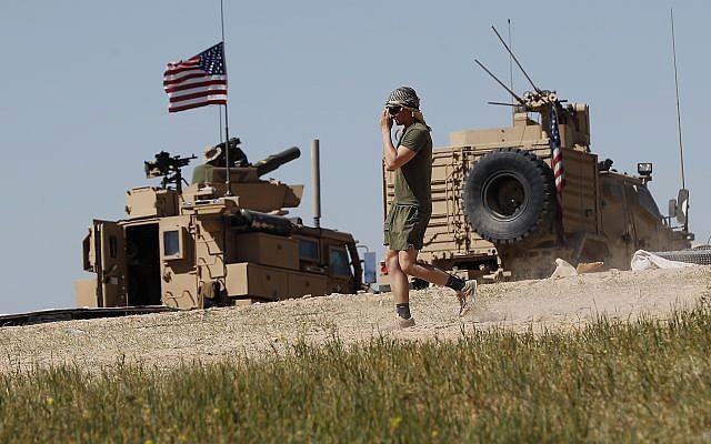 Un soldat américain se déplace sur une position nouvellement installée, près de la ligne de front tendue entre le Conseil militaire syrien de Manbij soutenu par les États-Unis et les combattants soutenus par la Turquie, à Manbij, au nord de la Syrie, le 4 avril 2018. (AP/Hussein Malla)