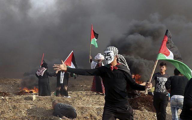 Des Palestiniens agitent leurs drapeaux nationaux tandis que d'autres brûlent des pneus près de la clôture de la frontière de la bande de Gaza avec Israël lors d'affrontements à l'est de la ville de Gaza, le 9 novembre 2018. (AP Photo/Adel Hana)