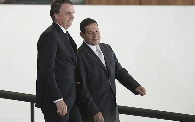 Le président brésilien Jair Bolsonaro, à gauche, se rend avec son vice-président Hamilton Mourao à une cérémonie au cours de laquelle les présidents des banques d'État du pays seront présentés au palais présidentiel Planalto de Brasilia, au Brésil, le lundi 7 janvier 2019. (Crédit :  AP / Eraldo Peres)